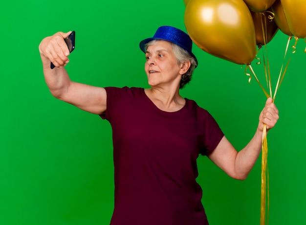 Blij bejaarde vrouw met feestmuts houdt helium ballonnen kijken naar telefoon op groen