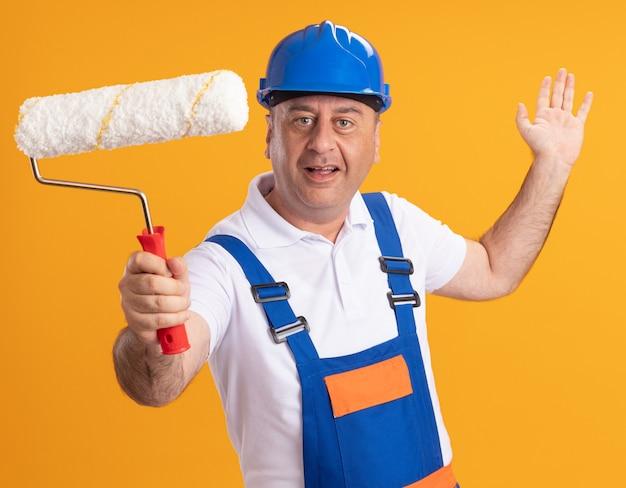 Blij blanke volwassen bouwer man in uniform staat met opgeheven hand en houdt rolborstel op oranje