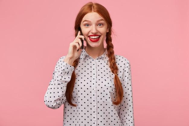 Blij blij blij opgewonden roodharig meisje houdt een telefoon in de hand bij het oor en kijkt met wijd open ogen en glimlach, onder de indruk