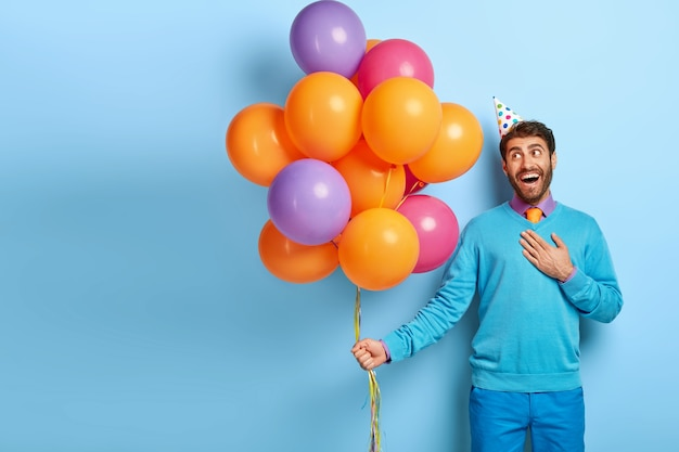 Blij blij man met verjaardagshoed en ballonnen poseren in blauwe trui