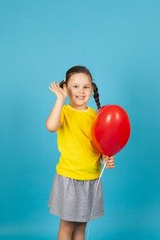 Blij blij meisje houdt een rode ballon in de vorm van een hart vast en zwaait met haar hand