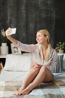 Blij blond meisje in zijden pyjama's smartphone kijken terwijl het maken van selfie op bed in de ochtend