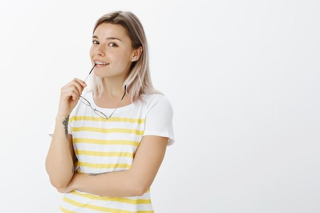 Blij blond meisje met een bril poseren in de studio