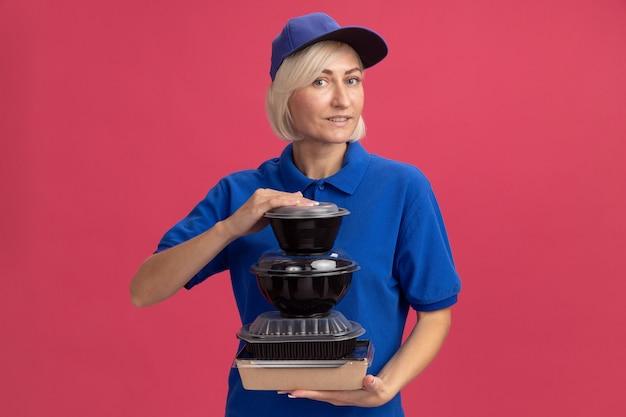 Blij blonde bezorger van middelbare leeftijd in blauw uniform en pet met papieren voedselpakket en voedselcontainers kijkend naar voorkant geïsoleerd op roze muur met kopieerruimte