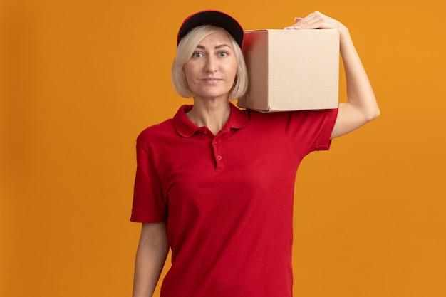Blij blonde bezorger van middelbare leeftijd in rood uniform en pet met kartonnen doos op schouder kijkend naar voorkant geïsoleerd op oranje muur met kopieerruimte
