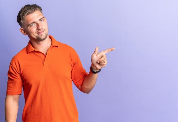 Blij blonde knappe man wijzend naar kant geïsoleerd op paarse muur met kopie ruimte