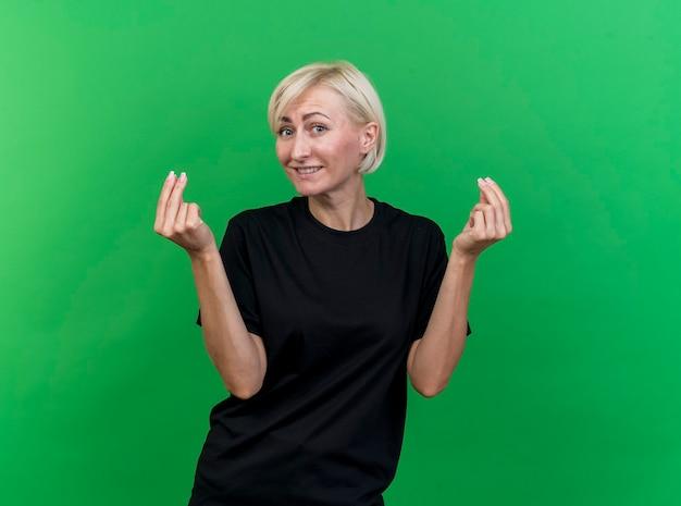 Blij blonde slavische vrouw die van middelbare leeftijd camera bekijkt die geldgebaar doet dat op groene achtergrond met exemplaarruimte wordt geïsoleerd