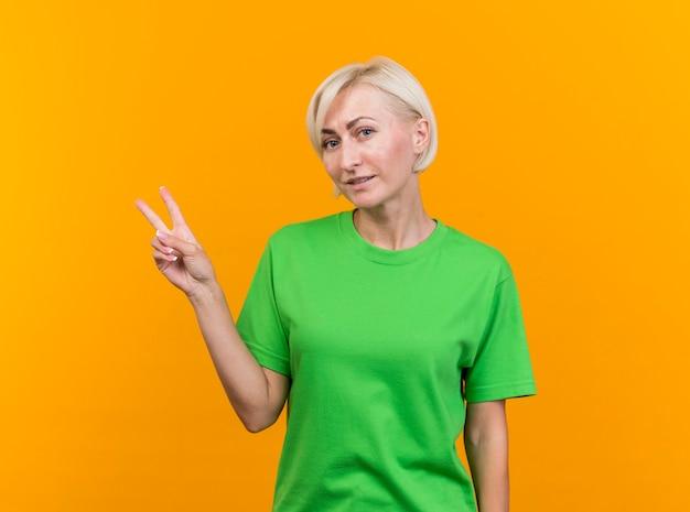 Blij blonde slavische vrouw die van middelbare leeftijd camera bekijkt die vredesteken doet dat op gele achtergrond met exemplaarruimte wordt geïsoleerd