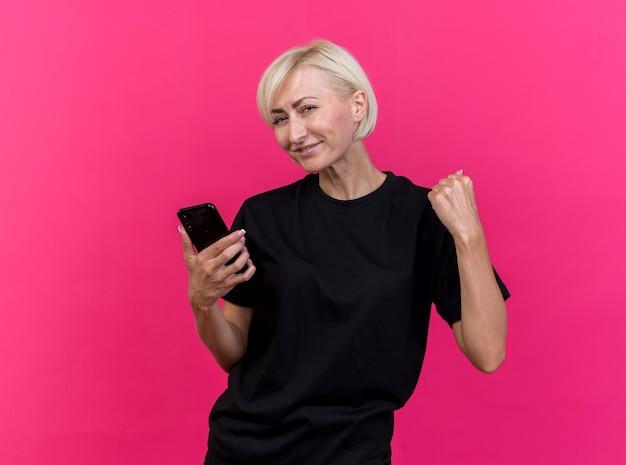 Blij blonde slavische vrouw die van middelbare leeftijd mobiele telefoon houdt die ja gebaar doet dat op karmozijnrode muur met exemplaarruimte wordt geïsoleerd