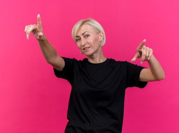 Blij blonde slavische vrouw van middelbare leeftijd die camera bekijkt die recht richt op karmozijnrode achtergrond wordt geïsoleerd