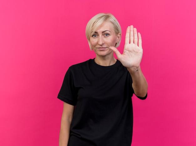 Blij blonde slavische vrouw van middelbare leeftijd die camera bekijkt die stopgebaar doet dat op karmozijnrode achtergrond met exemplaarruimte wordt geïsoleerd