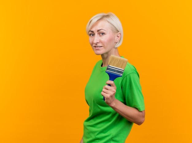 Blij blonde slavische vrouw van middelbare leeftijd die zich in de holdingsverfborstel van de profielmening bevindt die op gele muur met exemplaarruimte wordt geïsoleerd