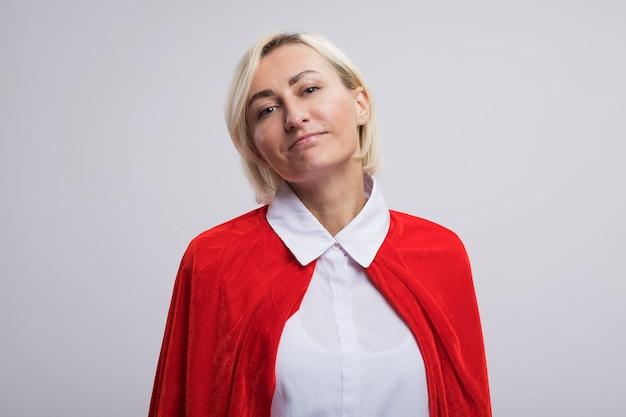 Blij blonde superheld vrouw van middelbare leeftijd in rode cape kijken naar voorzijde geïsoleerd op een witte muur