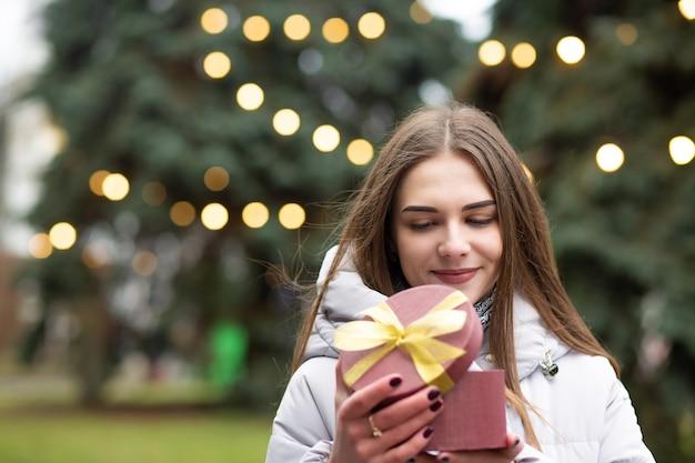Blij blonde vrouw met een geschenkdoos op straat. lege ruimte