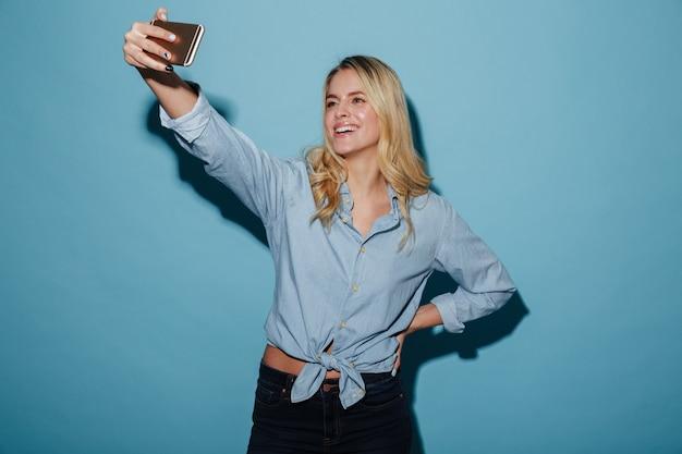 Blij blondevrouw die in overhemd selfie op smartphone maken