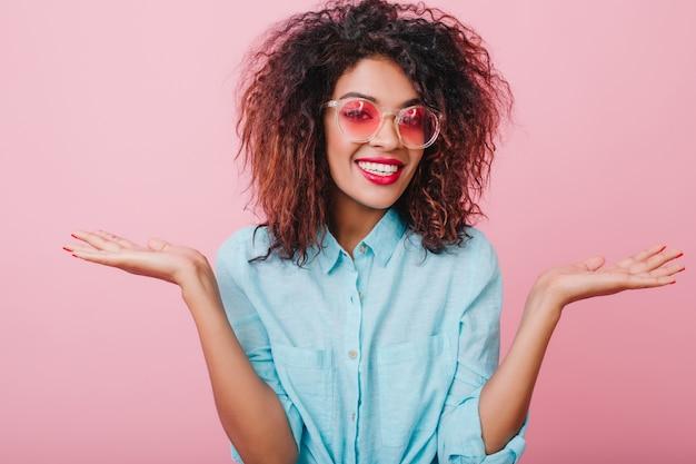 Blij brunette meisje met verrast glimlach poseren met handen omhoog. charmante mulatvrouw met bronzen huid die goede emoties uitdrukt.