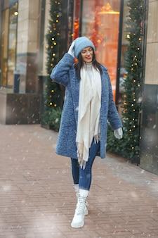 Blij brunette vrouw in jas wandelen in de stad bij sneeuwweer
