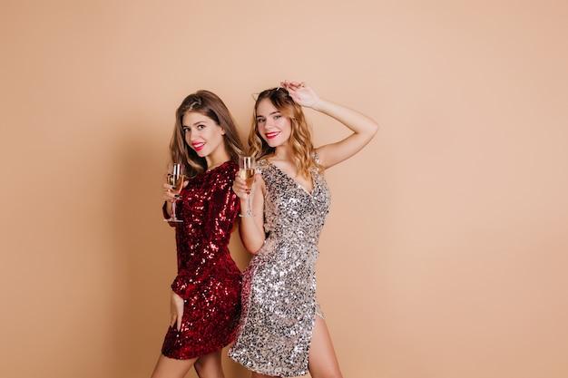 Blij brunette vrouw in mooie rode jurk staande naast gekrulde zus tijdens partij fotoshoot