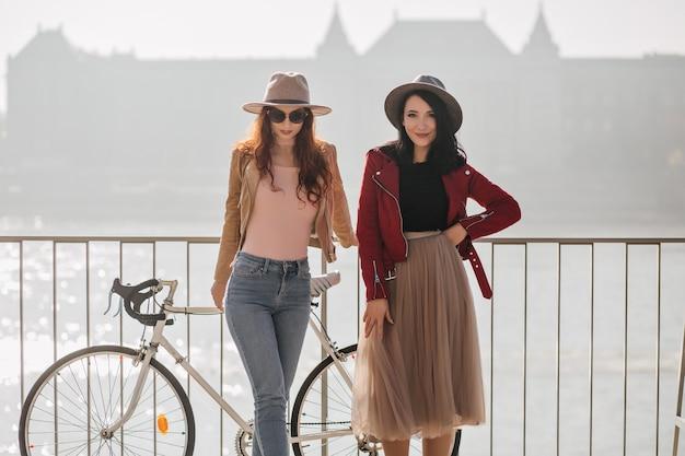 Blij brunette vrouw in romantische lange rok koelen met beste vriend aan kade met paleis op muur