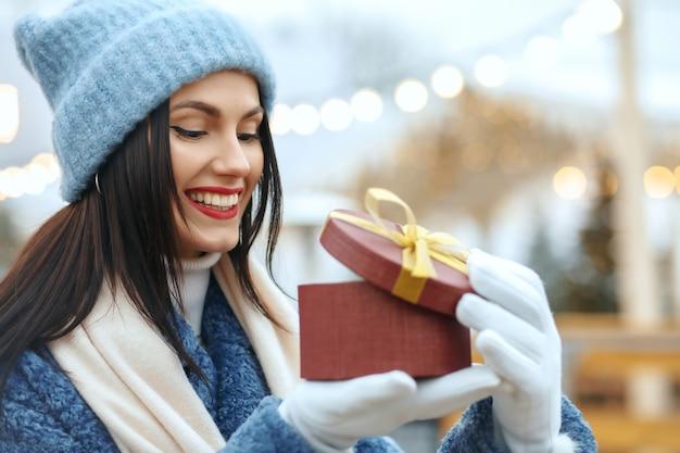 Blij brunette vrouw in winterjas met een geschenkdoos op kerstmarkt. ruimte voor tekst