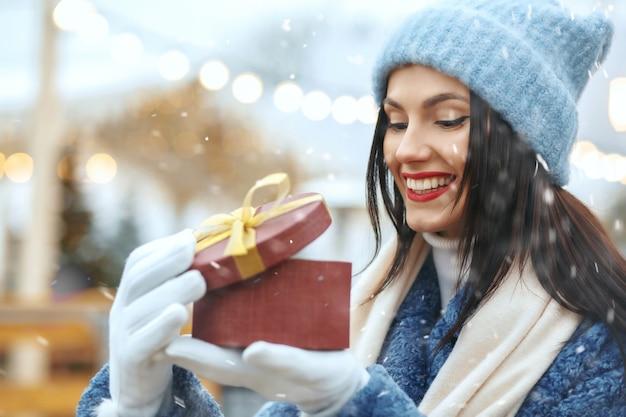 Blij brunette vrouw in winterjas met een geschenkdoos op kerstmarkt tijdens de sneeuwval. ruimte voor tekst