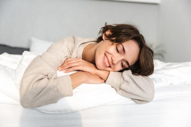 Blij brunette vrouw rust en geniet met gesloten ogen liggend op bed thuis