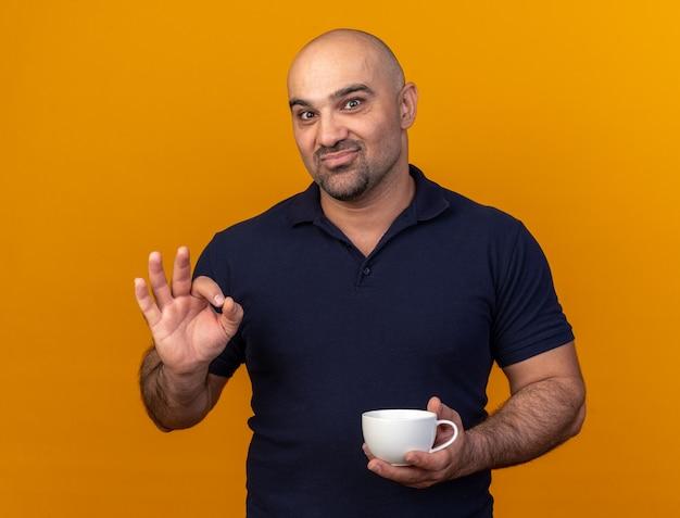 Blij casual man van middelbare leeftijd met kopje thee doen ok teken geïsoleerd op oranje muur