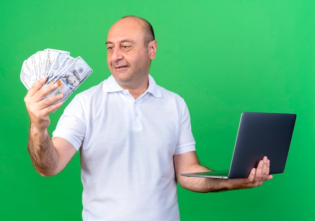 Blij casual volwassen man met laptop en contant geld in zijn hand kijken