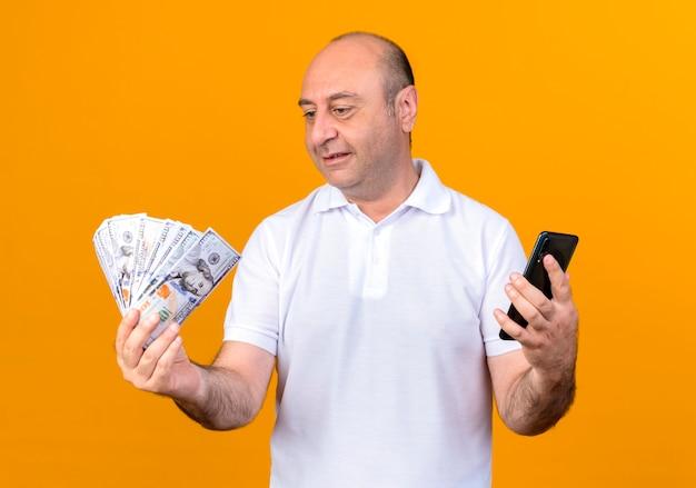 Blij casual volwassen man met telefoon en kijken naar geld in zijn hand geïsoleerd op gele achtergrondkleur