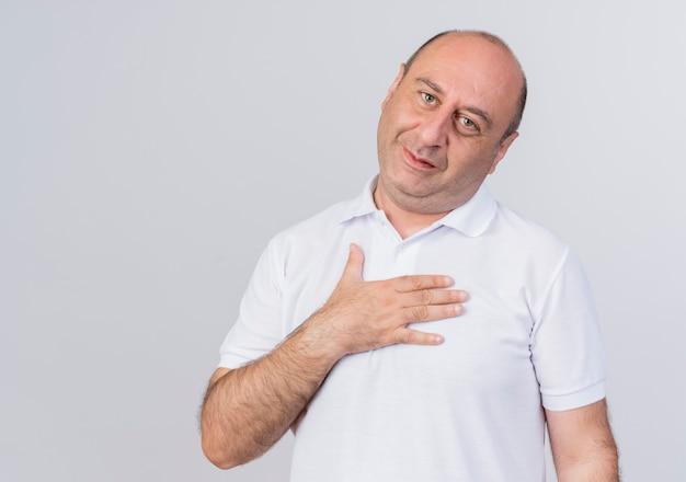 Blij casual volwassen zakenman hand zetten borst kijken camera geïsoleerd op een witte achtergrond met kopie ruimte