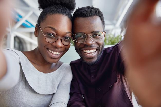 Blij dat afrikaanse vrienden graag samen rusten, positieve uitdrukkingen hebben, foto maken, hand strekken als selfie maken, foto's delen op sociale netwerken.