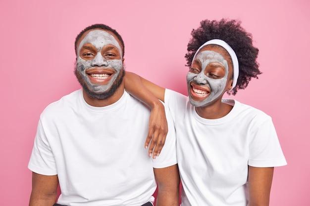 Blij dat afro-amerikaanse echtpaar een gezichtsmasker van klei toepast voor gezichtsverzorging, een glimlach heeft gelukkig een goed humeur