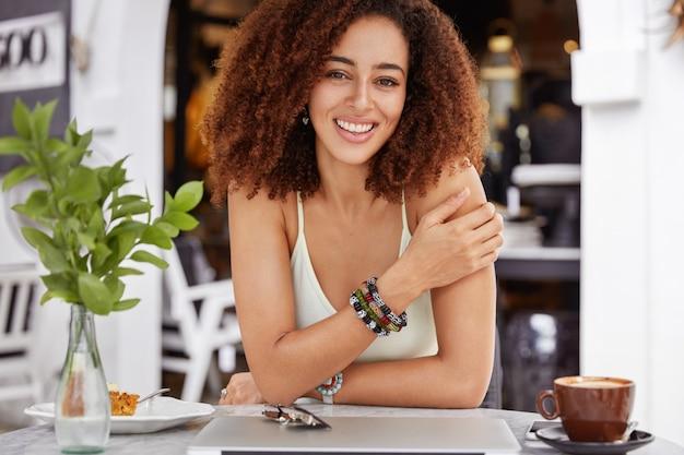 Blij dat afro-amerikaanse jonge vrouw alleen rust in de coffeeshop, heeft een verrukkelijke blik, rust na het werk op een laptopcomputer, heeft een positieve uitdrukking.