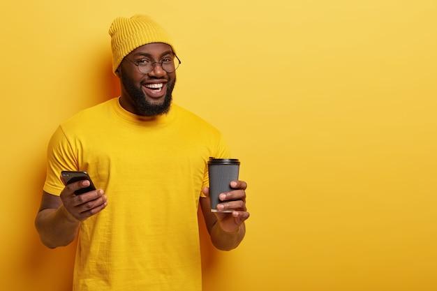 Blij dat afro-amerikaanse man nieuwsfeed leest in sociale netwerken, geniet van warme drank uit een wegwerpbeker