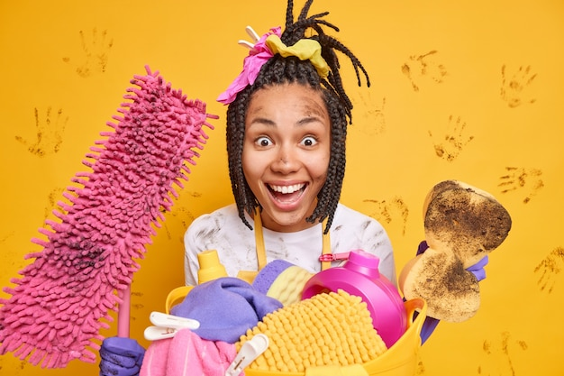 Blij dat afro-amerikaanse vrouw met vlechten vuile spons vasthoudt en dweil vrolijk naar de camera kijkt, verwijdert vuil overal geïsoleerd over gele muur