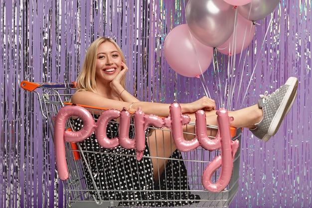 Blij dat blonde vriendin in winkelwagen, verjaardag viert, modieuze kleding draagt, vormt over paarse muur met lucht ballonnen, positieve emoties uitdrukt. mensen, viering, partijconcept
