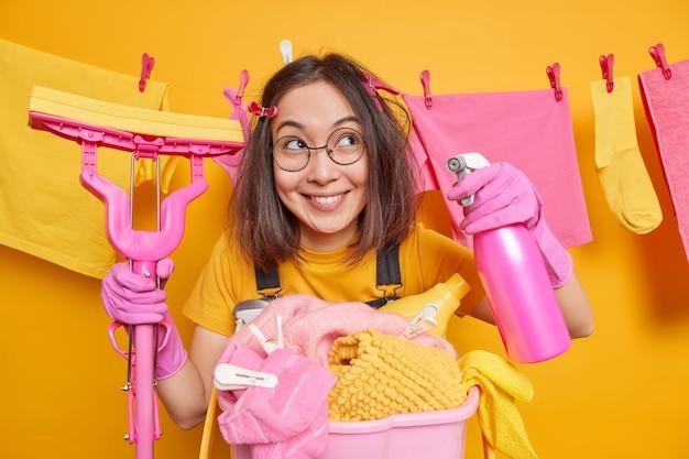 Blij dat de aziatische huishoudster de lenteschoonmaak houdt, wasmiddel vasthoudt en dweil wast het huis van stof kijkt met een gelukkige doordachte uitdrukking opzij staat in de buurt van wasmand met waslijn erachter