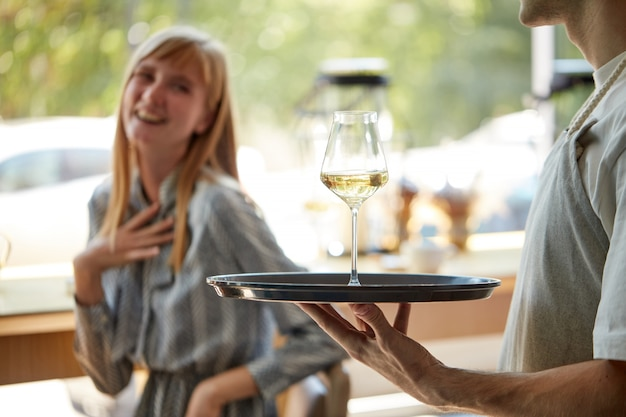 Blij dat de ober glas champagne op dienblad naar klanten brengt Premium Foto