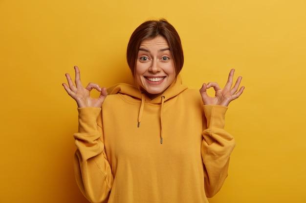 Blij dat donkerharige jonge vrouw zegt dat het goed klinkt, bevestigt iets, alles onder controle en gaat geweldig, keurt promo goed, heeft een blije uitdrukking, is het eens met de persoon, draagt een geel sweatshirt.