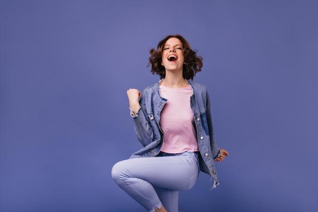 Blij dat donkerharige vrouw positieve emoties uitdrukt. actief mooi meisje dat met glimlach springt.