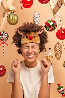 Blij dat een donkere vrouw met krullend, borstelig haar gebalde vuisten opheft en succes viert bereidt zich voor op het vieren van kerstmis draagt poses in vrijetijdskleding