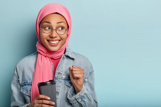 Blij dat een jonge vrouw met een donkere huidskleur haar vuist balt, afhaalkoffie vasthoudt en een optische bril draagt