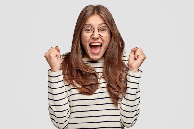 Blij dat europese vrouw een bril draagt, gebalde vuisten van opwinding, een ronde bril en een losse trui draagt, roept van geluk, heeft donker haar en een prettige uitstraling, modellen over een witte muur