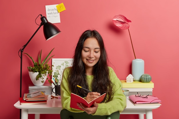 Blij dat geconcentreerde vrouw gefocust in notitieblok, ideeën opschrijft voor opstel of onderzoekswerk, recensie verzint, poseert tegen werkplek met bureaulamp