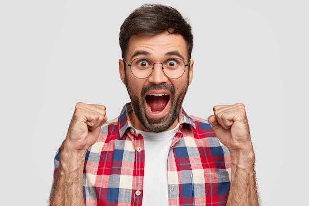 Blij dat gelukkige jonge man zijn mond opent, vuisten balt en triomfantelijk roept, gekleed in een geruit overhemd, staat tegen een witte muur. een man met stoppels voelt zich kampioen of winnaar