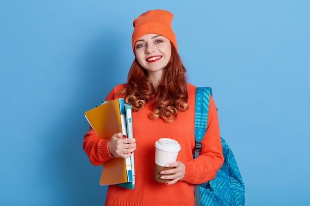 Blij dat gemberstudente na colleges koffiepauze heeft, geniet van warme drank, rugzak op rug heeft