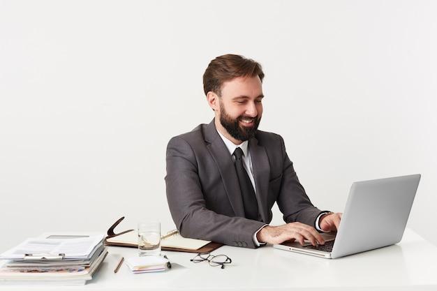 Blij dat glimlachende aantrekkelijke bebaarde zakenman, topmanager achter desktop op kantoor zit, werkt voor zijn laptop, gekleed in een duur pak met stropdas, geniet van zijn werk.