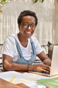 Blij dat hipster-softwareontwikkelaar de applicatie op laptopcomputer aanpast, verbonden met draadloos internet, toetsenborden
