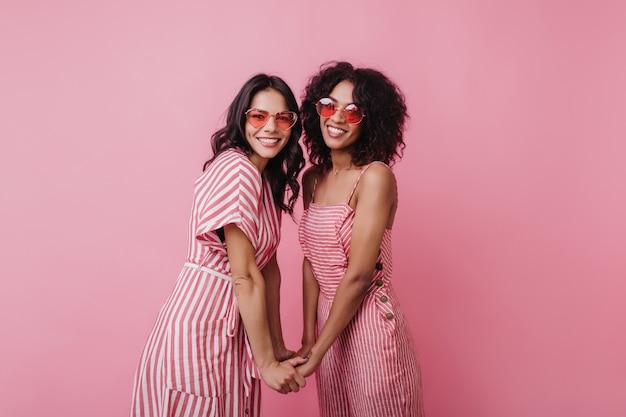 Blij dat jonge dames elkaars hand vasthouden tijdens het poseren. binnen schot van lachende gelukkige vrouwelijke modellen draagt zomerkleding.