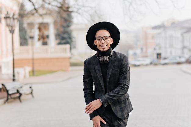 Blij dat jonge man in een donker pak en hoed rondlopen in het park in de ochtend. buiten foto van lachende afrikaanse mannelijk model in trendy kleding